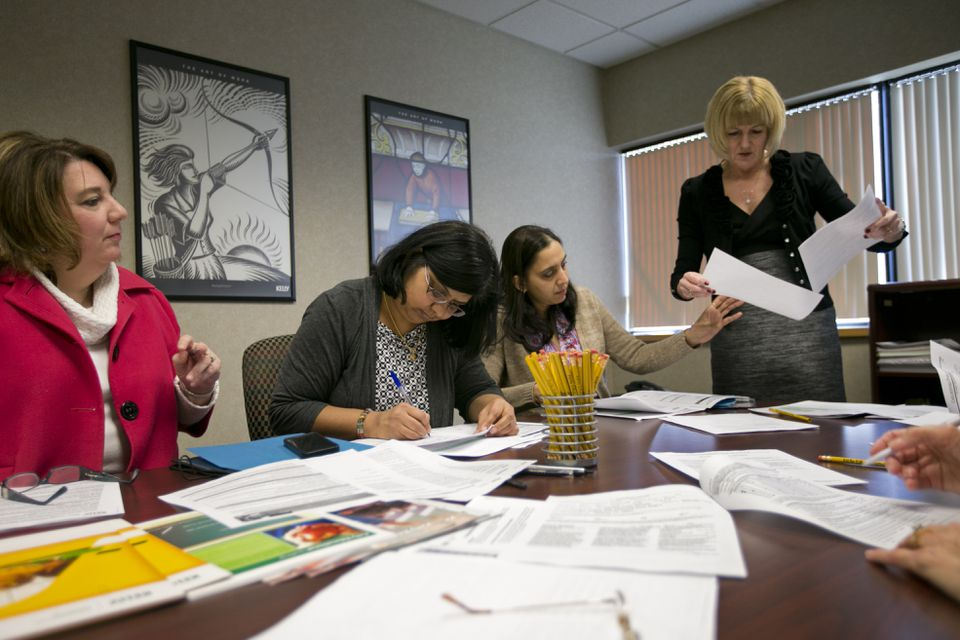 At an orientation for substitute teachers at Kelly Services in Burlington, (from left) area manager Faith Burke helps Divya Lalwani and Kavita Deshmukh, both of Chelmsford, fill out forms, along with Linda Harden, supervisor of educational staffing at Kelly.
