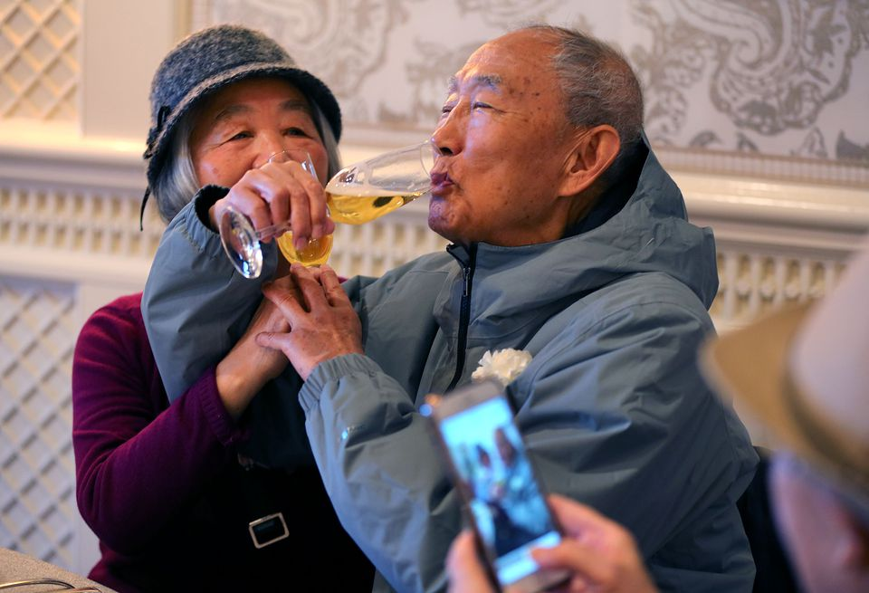 Jian Guan (left) and her husband of 58 years, Shi, interlocked their arms as they toasted one another at the annual Golden Wedding Anniversary Celebration.