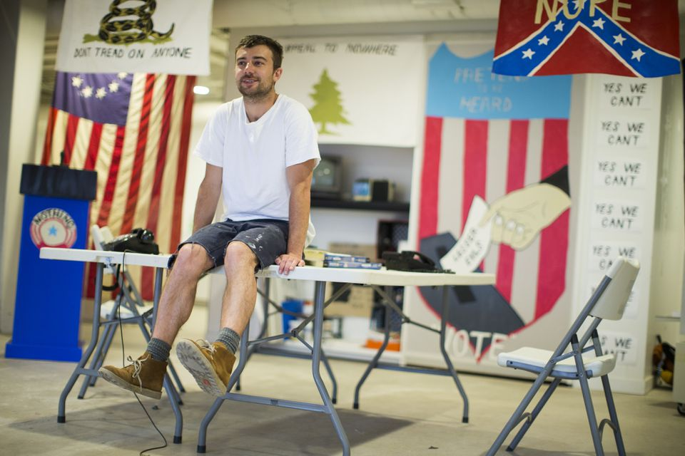 """Artist Pat Falco sits in his installation """"Boston Campaign Headquarters"""" at Faneuil Hall Marketplace."""