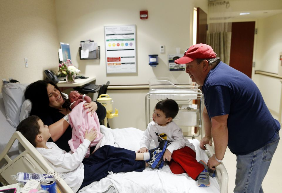 Jennifer Scalise lifts up Harper Grace as her husband Mark, who delivered the baby, watched over their other two sons.