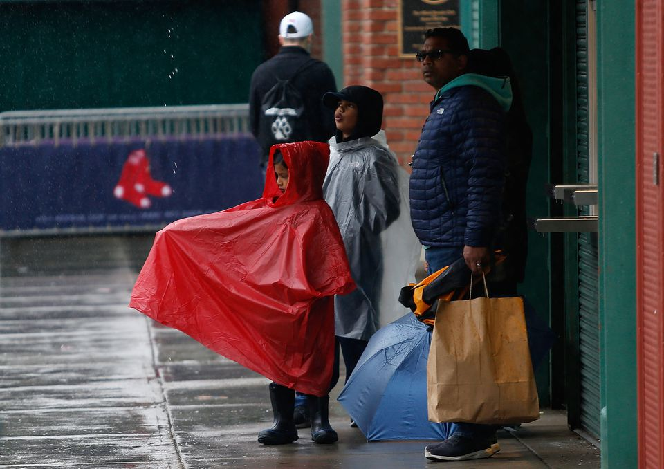 A family waits for a ride outside of Fenway Park after finding out that the game between the Red Sox and the Tigers was rained out Monday.