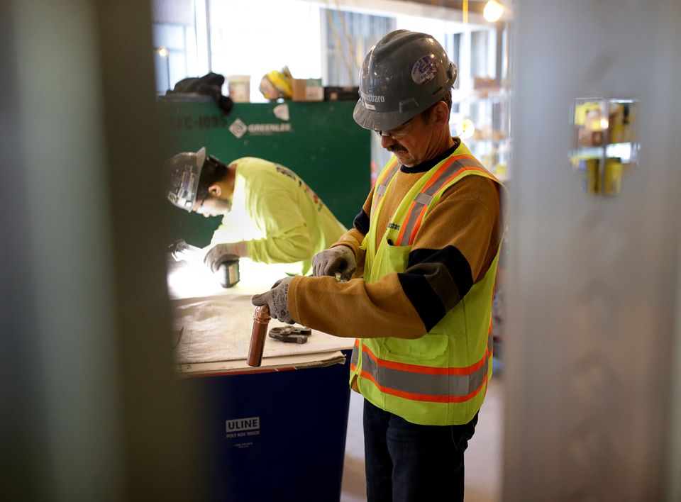 John Kuks, a Cannistraro employee, works on a shower assembly at a laboratory under construction on Binney Street in Cambridge.