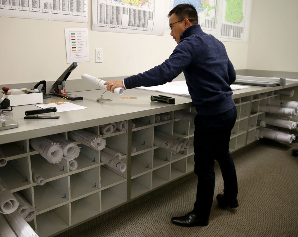 Bao Lam processes bid documents and plans at the company's Watertown headquarters.