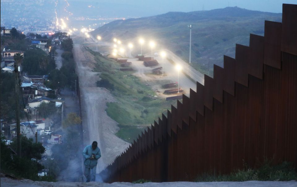A man walked on the Mexican side of the US-Mexico border before sunrise Saturday in Tijuana, Mexico.