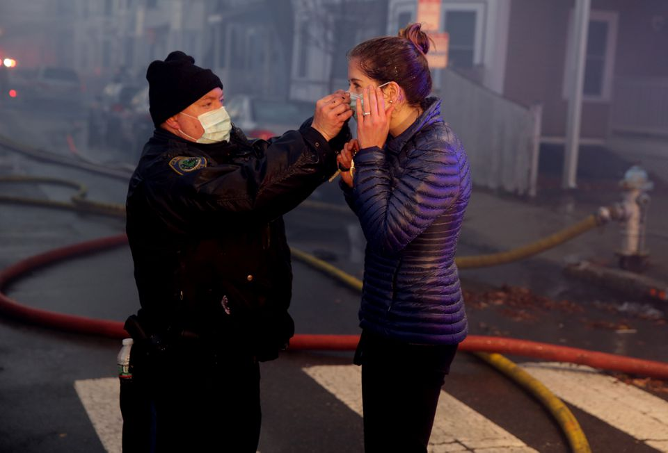 A Cambridge police officer helped a woman at the scene of the fire.