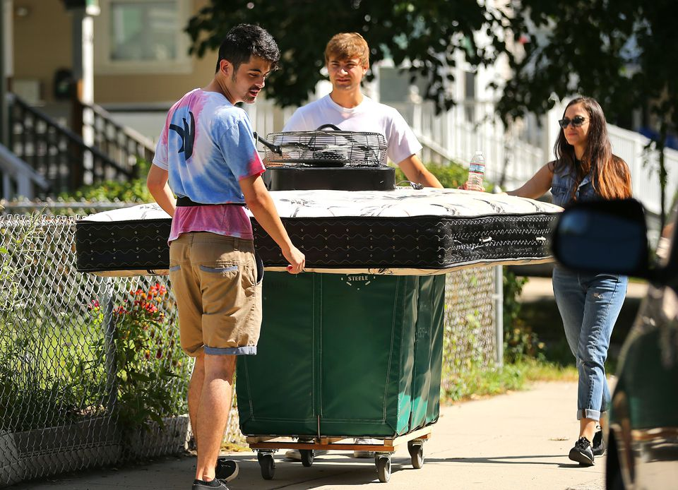Students moved a mattress along a sidewalk on Ashford Street in Allston.