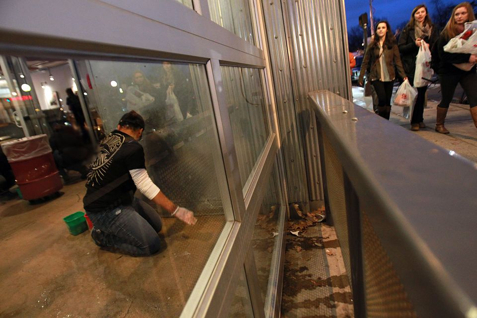 Workers cleaned the Chipotle restaurant in Cleveland Circle that was closed after more than 80 people fell ill.