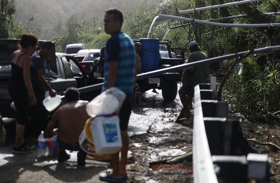 People fill containers with water funneled through pipes from a mountain stream on Oct. 19, nearly one month after Hurricane Maria struck, in Utuado, Puerto Rico.