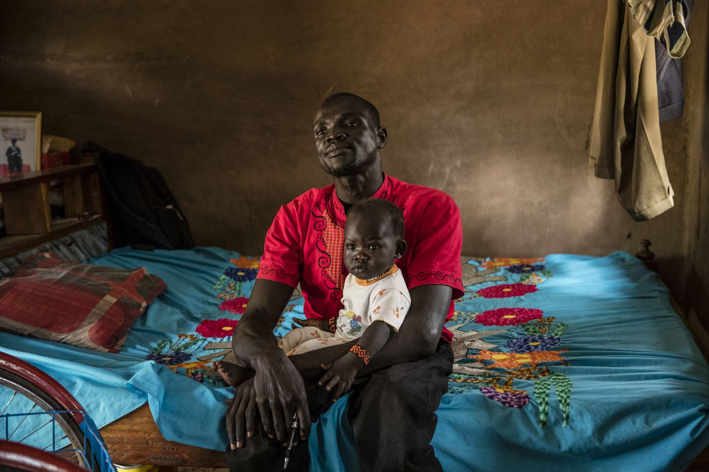 Bol Daniel Maduk, who contracted polio as a child, held his infant daughter on his lap in the compound where he lives in the UNHCR refugee camp in Kakuma.