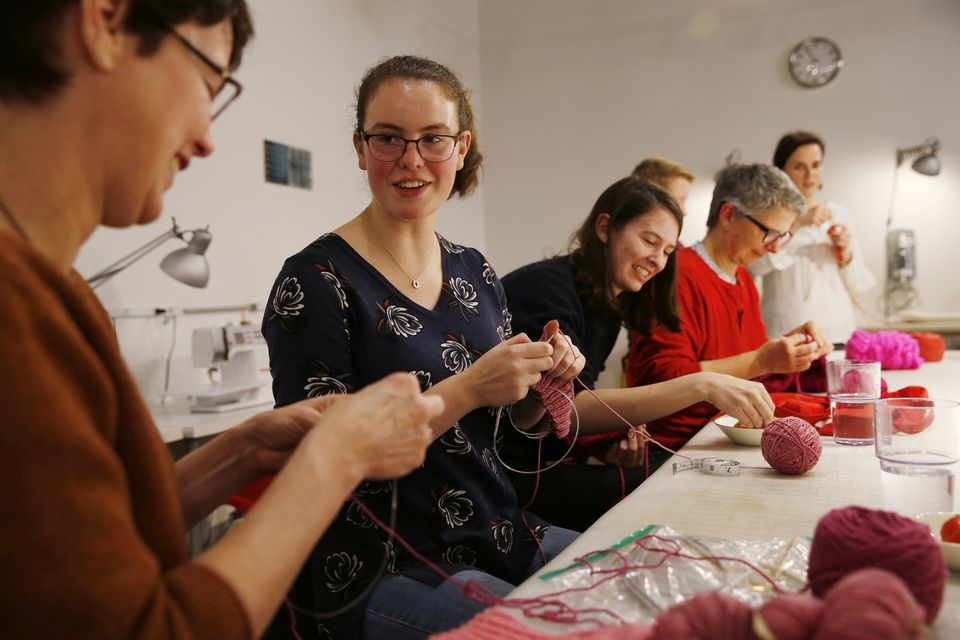 Lestra Litchfield of Cambridge (left) joked with her daughter, Lestra Atlas, as they and others knitted hats last week at Gather Here in Cambridge's Inman Square.