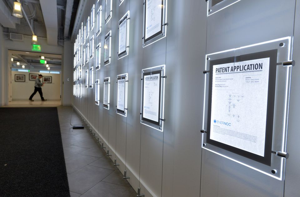 A wall of illuminated patent applications lines a corridor at EnerNoc's One Marina Park Drive headquarters.