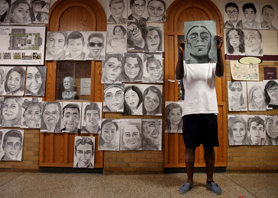 Senior Phillip Sossou held his self-portrait while posing with his artwork at Boston Latin School.