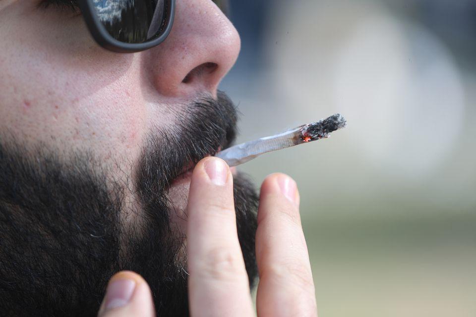A marijuana enthusiast smokes a marijuana cigarette in April in the Boston Common.