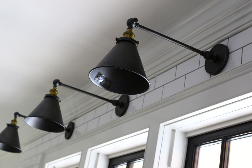 Sconces from RH are perched over windows above the kitchen sink.