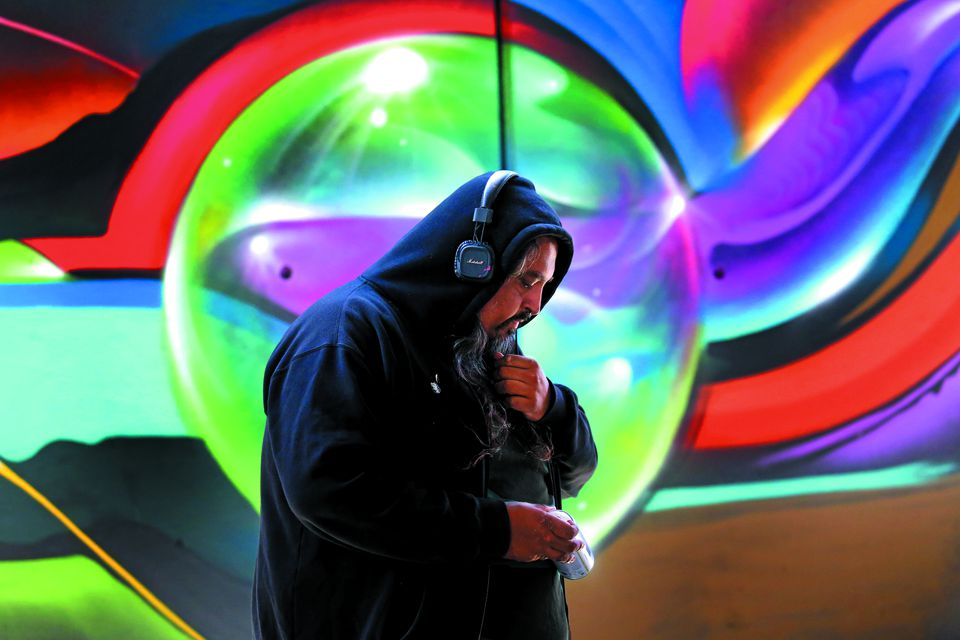 """Artist Vyal Reyes, an artist from L.A., works on his mural at """"Ink Underground."""""""