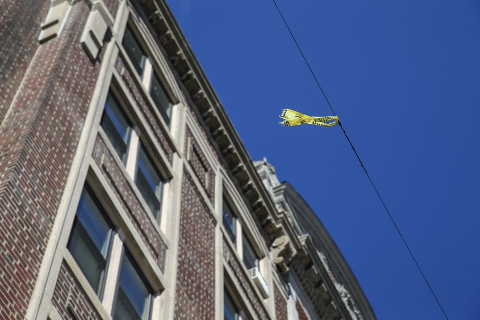 A piece of caution tape hangs on a power line outside of Our Lady's Guild House in Fenway.