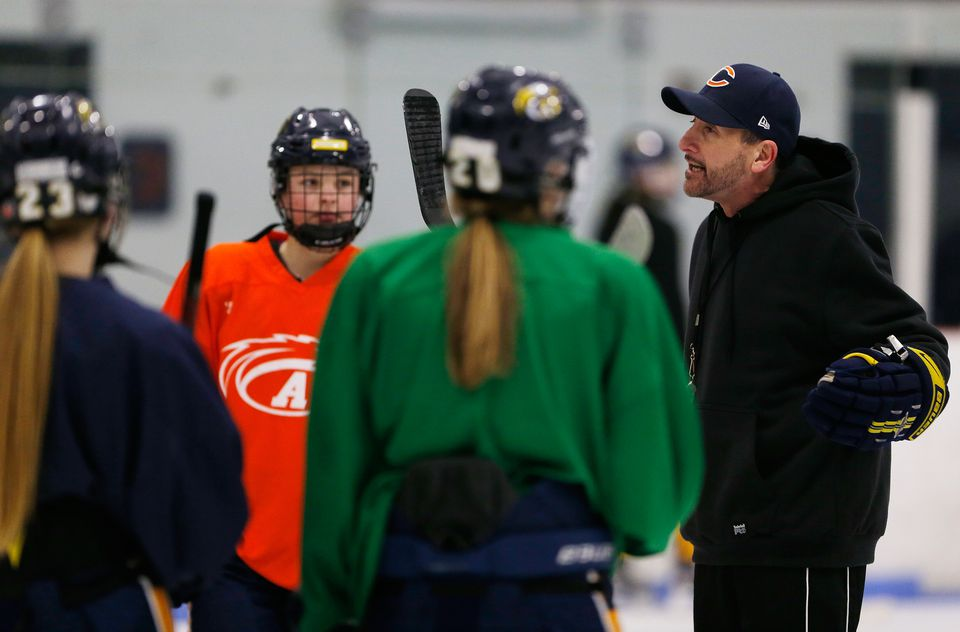 Andover girls' hockey coach Kevin Drew (right) talks to his players during a recent practice.
