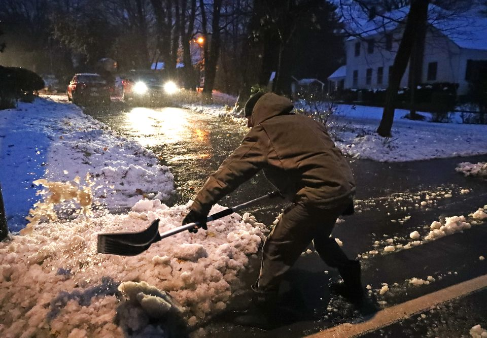 Rob Noyes of Hingham shoveled snow in front of his house on Friday before going to work.