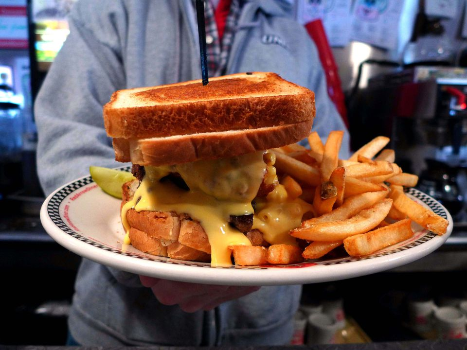 An impressive sight, the Newton Burger consists of a burger with lettuce, tomato, onion, and a scoop of deep-fried macaroni and cheese layered between two grilled cheese sandwiches.