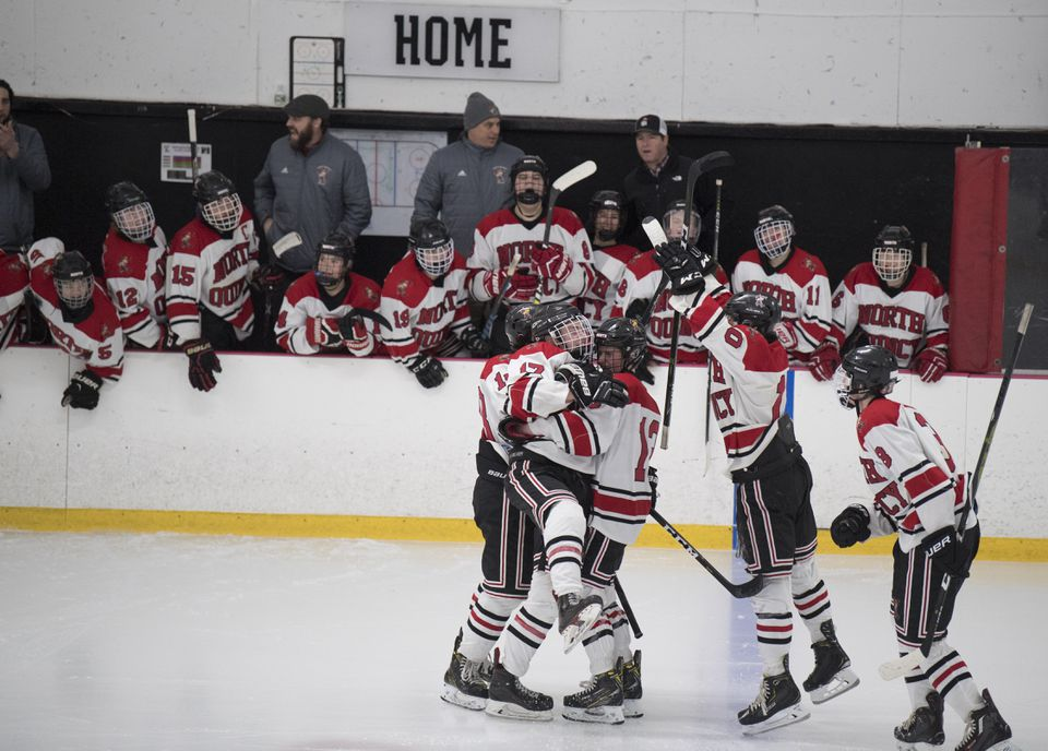 Senior forward Noah Wine (17) is mobbed by his North Quincy teammates after scoring a goal against Duxbury.