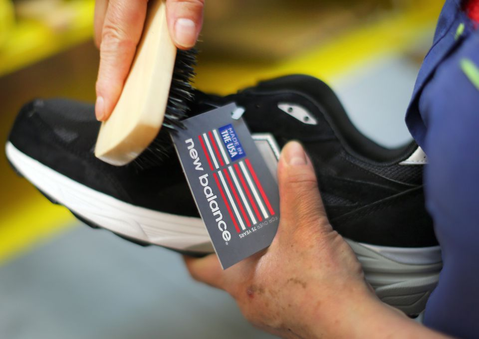 A running shoe is brushed in a final step before boxing them in Lawrence.