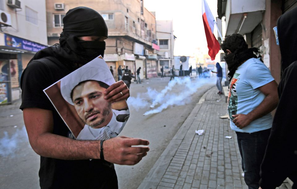 A masked Bahraini anti-government protester holds a picture of jailed Shiite cleric Sheik Ali Salman, the head of the opposition al-Wefaq political association, as riot police fire tear gas canisters in Jan. 2015. Last month, Bahrain said it has suspended all activities by Al-Wefaq, the largest Shiite opposition political group, and frozen its assets amid a widening crackdown on dissent.