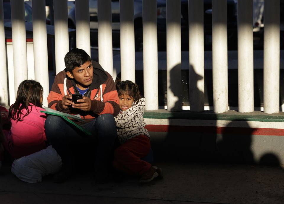 A migrant who did not give his name waited with his children as they sought asylum in the United States, at the border in Tijuana, Mexico.