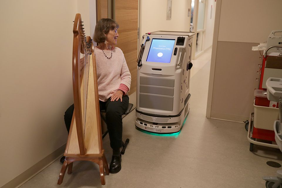 Margot Chamberlain paused in playing her harp so that Lucy, the pharmacy robot, can pass by at Dana-Farber Cancer Institute. The robot is being developed to take drugs to patients.