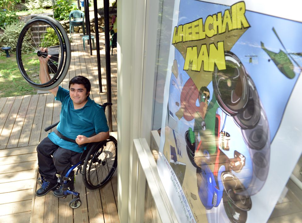Mohammad Sayed with a poster of his comic book character Wheelchair Man. The illustration is Arielle Epstein.