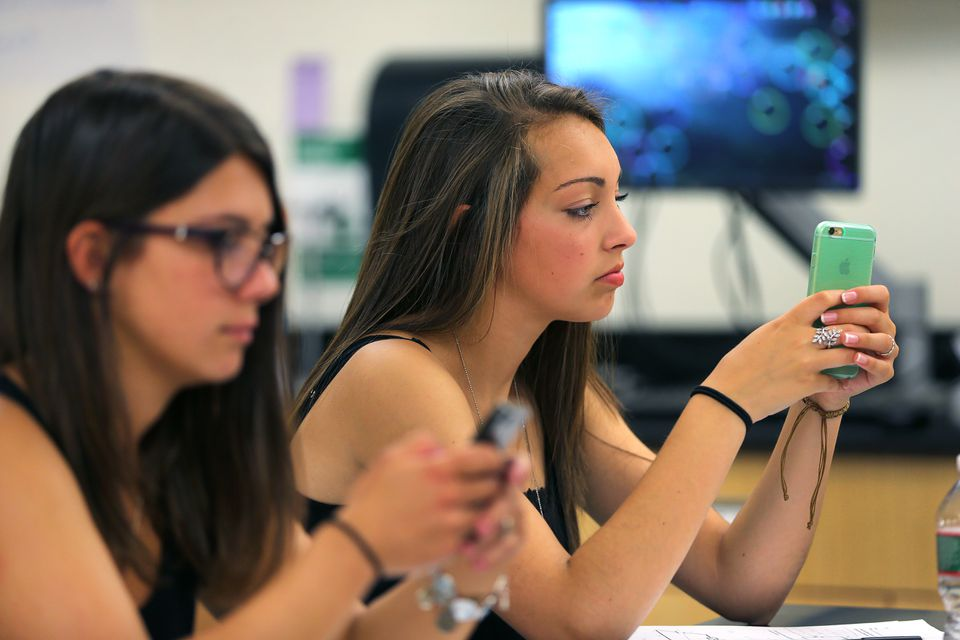 Melrose High students Beatrice Affatato (left) and Miranda Lombardo used smartphones in Blair Cochran's physics class.