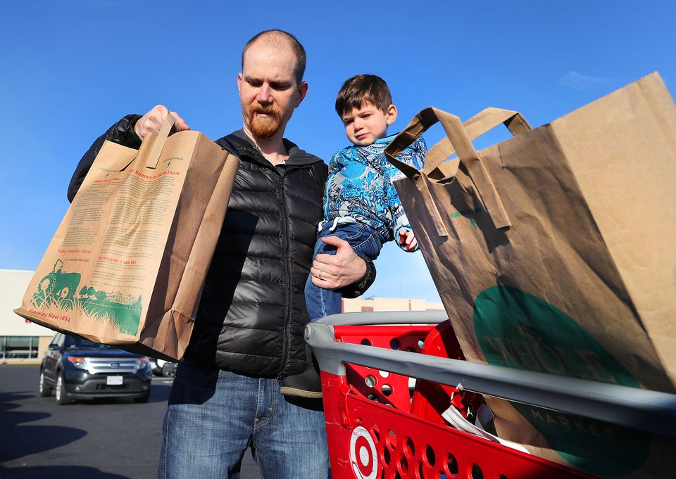 John Lynch held his son Owen, 2, as he puts his reused paper bags into his trunk after shopping at Target.