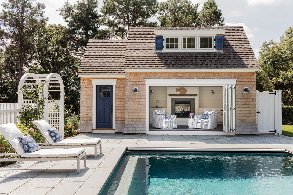 The pool house has a lovely lounge and play space that opens to the water. Shiplap wall paneling adds to the coastal charm while the fireplace and heated floor ensure that everyone stays warm.