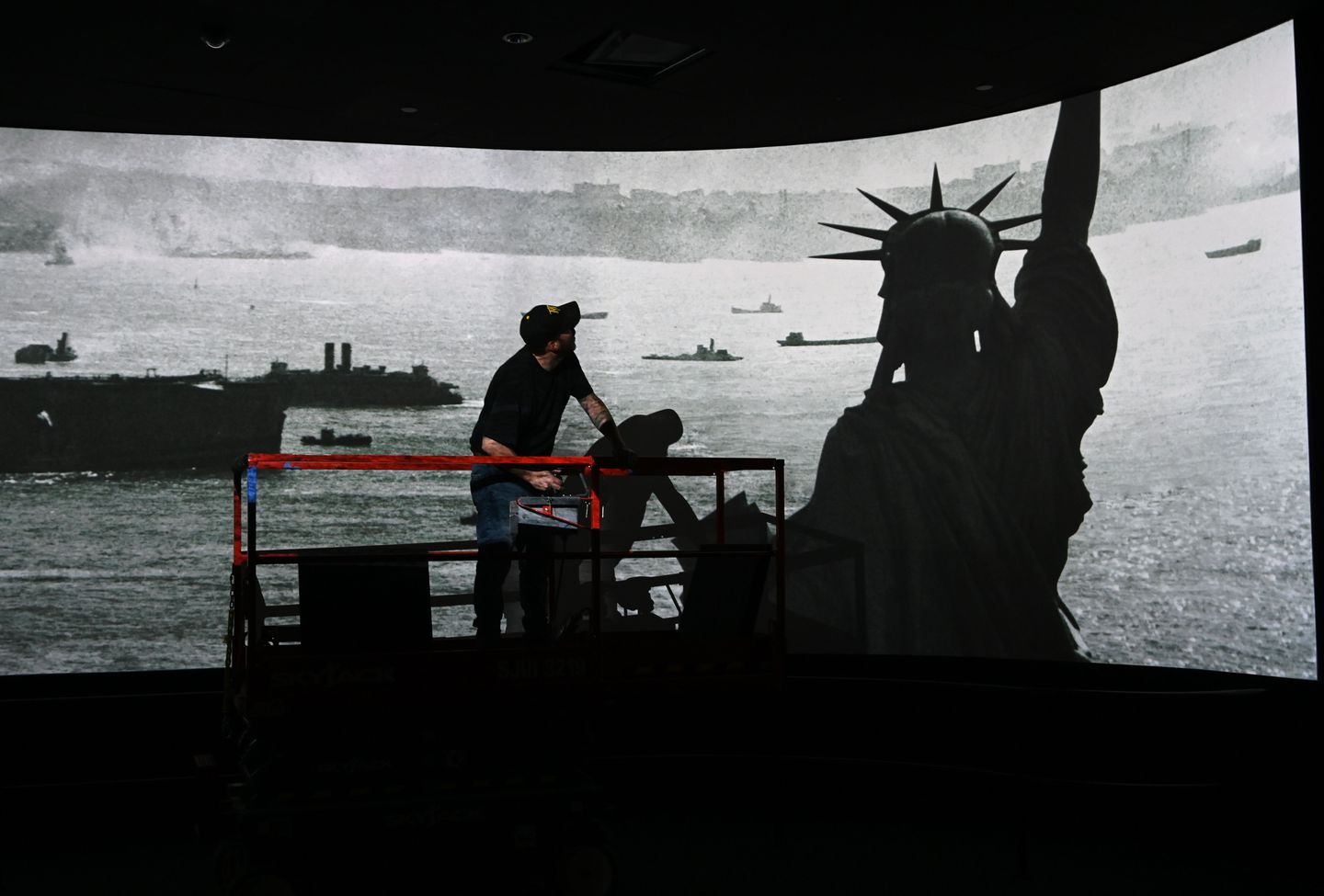 A worker put finishing touches on the ceiling in a room showing a movie during a press preview at the new Statue of Liberty Museum.