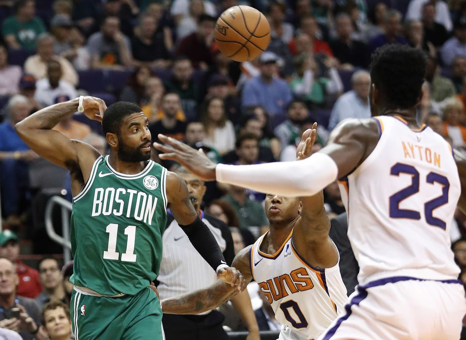 Celtics guard Kyrie Irving tosses a pass as Suns defenders DeAndre Ayton (22) and Isaiah Canaan close in.