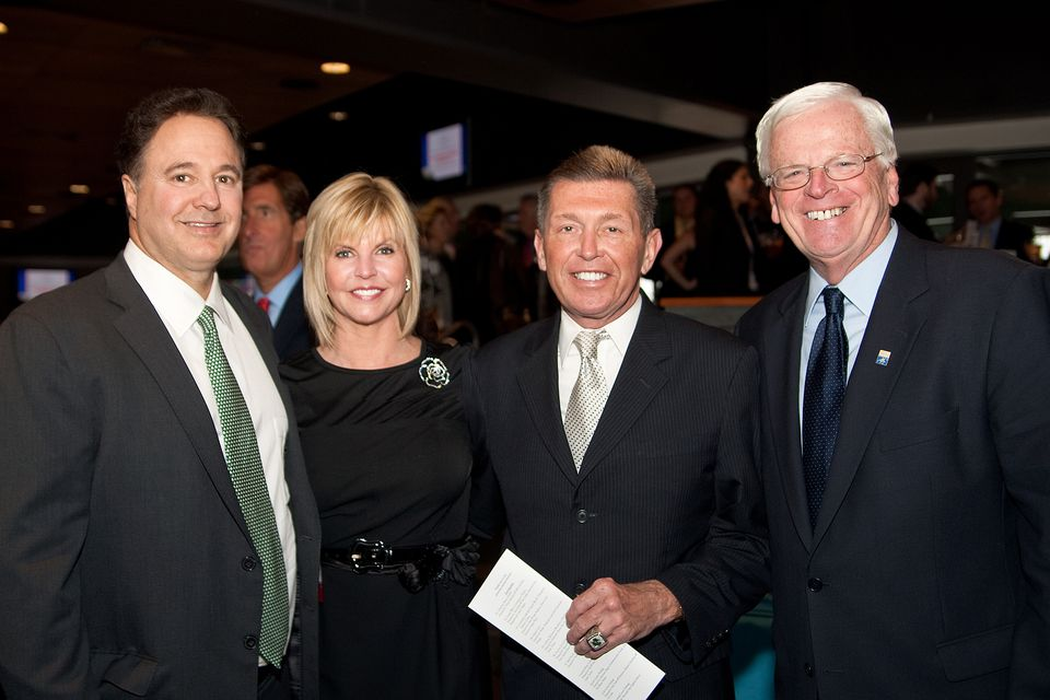 George Regan (second from right) with Julie Kahn, a Regan employee who says she plans to step off the Suffolk board when her term expires this spring, Celtics co-owner Steve Pagliuca (left), and Suffolk trustee Bob Sheridan at an event at Fenway Park in 2011.