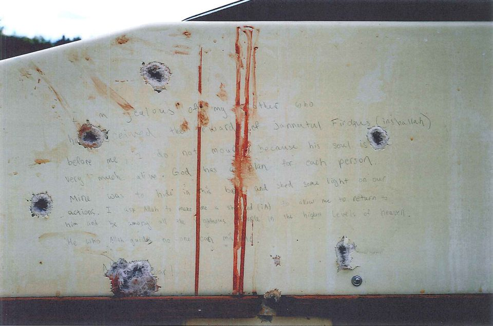 Photographs were taken inside the private boat that Dzhokhar A. Tsarnaev was hiding in before he was captured by police in the backyard of a Watertown home on April 19, 2013. Tsarnaev wrote the notes with a pencil. The bullet holes are from shots fired into the boat by police, according to a witness who testified Tuesday about the discovery of the writings.