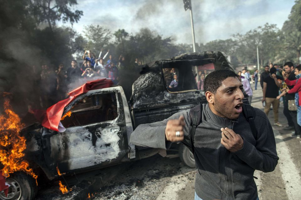 A student at Cairo University stands near a burning police vehicle during a demonstration Dec. 1 in support of a fellow student who was killed in clashes with Egyptian security forces.