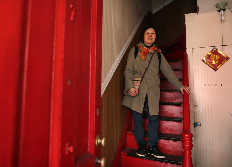Wendy Yee on the stairs of her two-story row house at 7 Johnny Court.