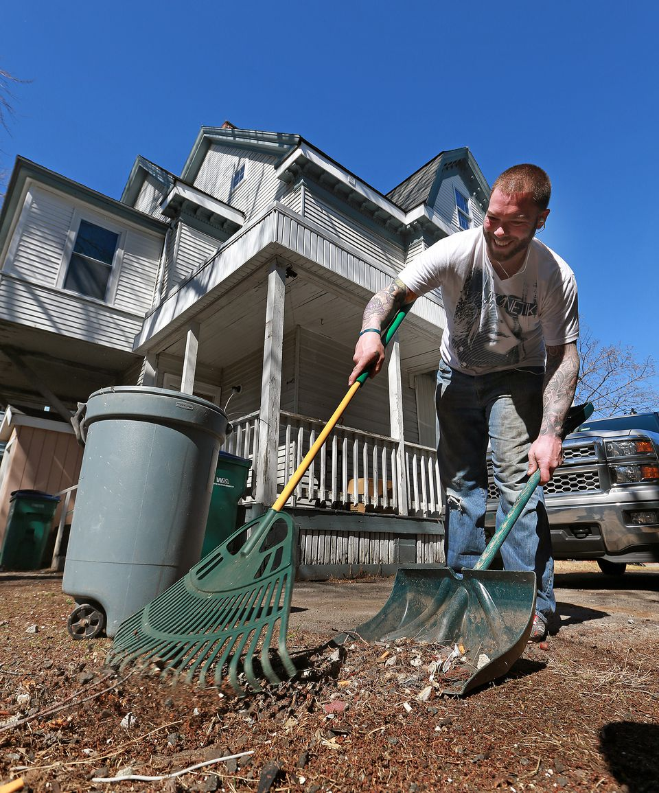 Joe Richards, a resident of Chelsea's House, the first sober house to meet state standards and be certified, did some raking in the back yard.