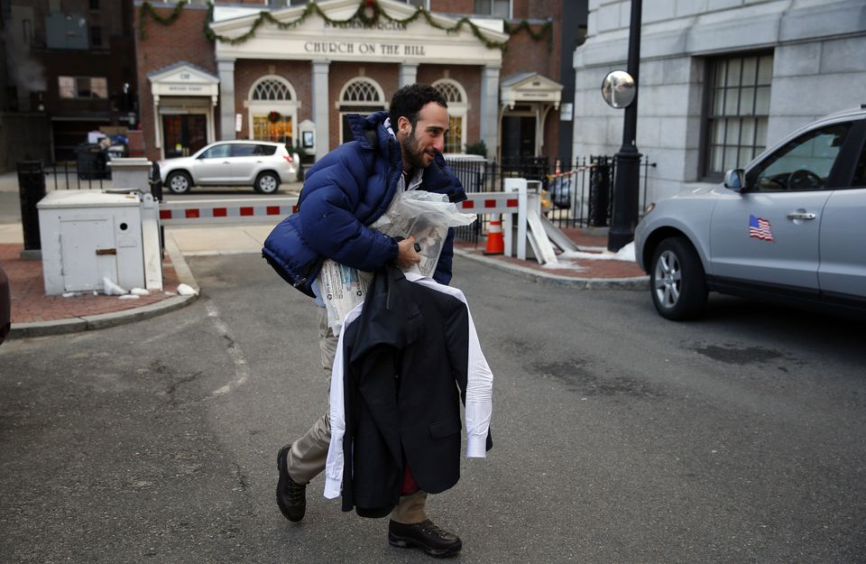 Reporter Josh Miller carried his suit and a bundle of Sunday newspapers to the State House as he arrived for an interview after spending the early-morning hours help with deliveries.