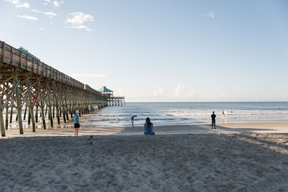 Visitors take in the surf at Folly Beach.