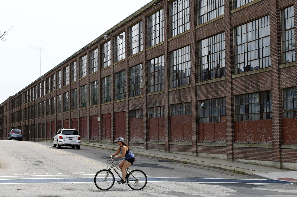 A bicyclist passed the former Draper Corp. factory (also seen below), which closed nearly 40 years ago. The property has stood vacant, despite multiple plans to redevelop.