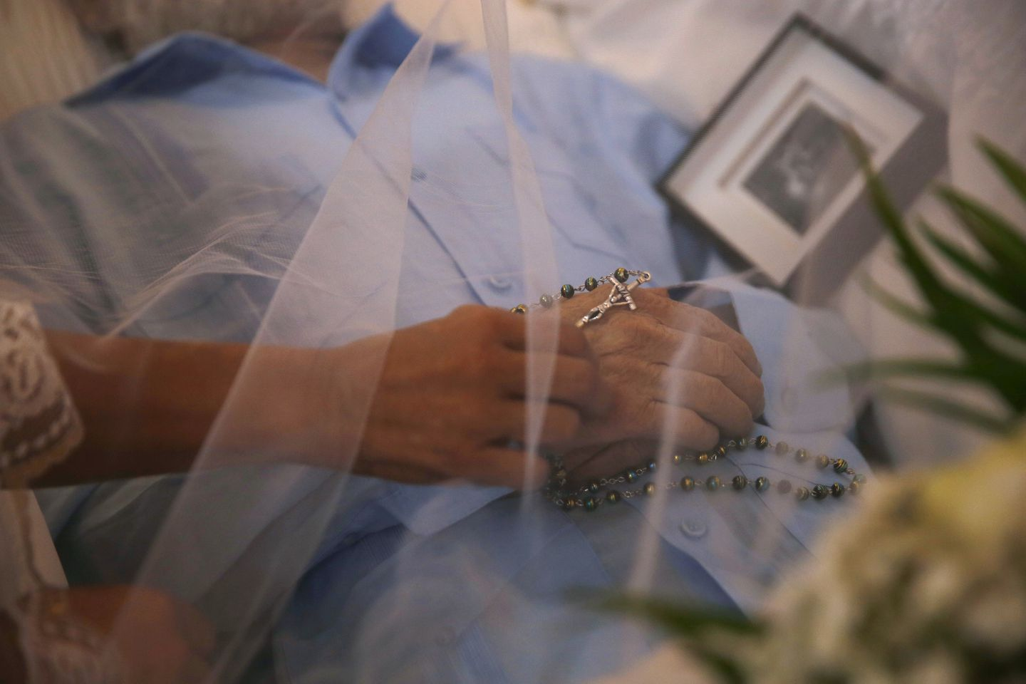Ana Ruiz reached out to adjust the rosary beads on her husband's hand during his wake.