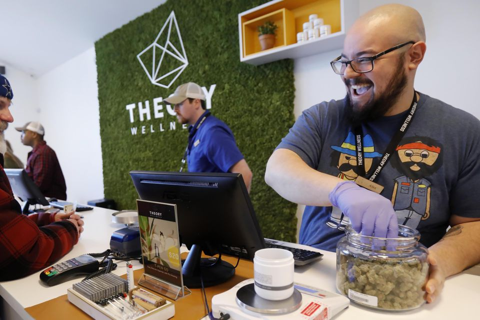 Alex Premoli makes the first sale to a customer on the opening day of recreational marijuana sales at Theory Wellness in Great Barrington on Jan. 11.