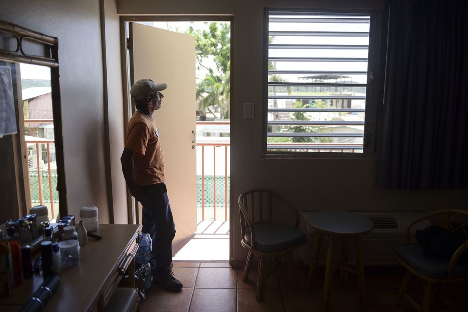 Fernando Muniz looked out from his hotel room, where he has taken refuge for months after Hurricane Maria caused damage to his San Juan residence.
