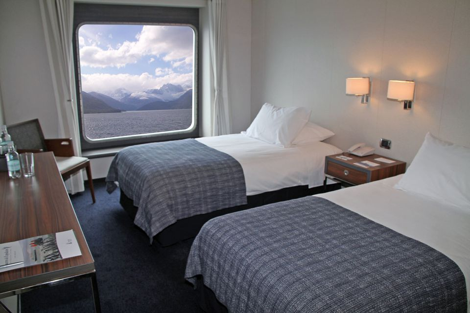 A comfortable stateroom on the Ventus Australis features floor-to-ceiling windows.