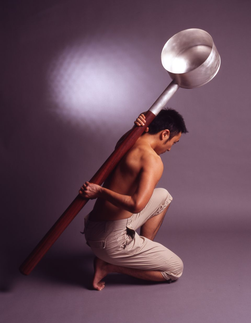 """A man bracing Chien-Wei Chang's """"Huge Ladle"""" against his back."""