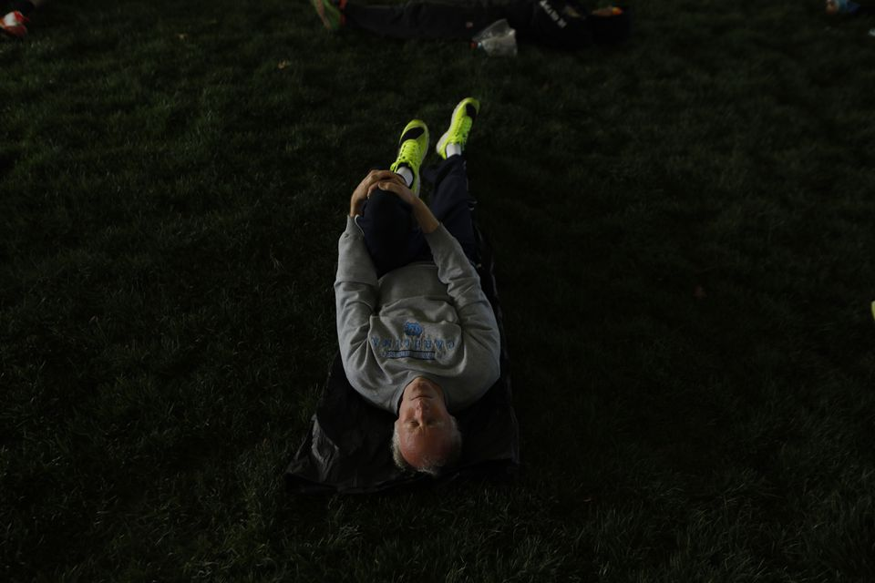 A runner stretched at the athelete's village in Boston.