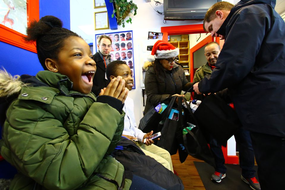 Mayor Martin J. Walsh handed gifts to Chloe Boutin, and her brother, Chris, both 10, Saturday at Fwresh Salon and Spa. Walsh and Police Commissioner William B. Evans walked through the Bowdoin-Geneva area with city officials and police officers, handing out gifts to every child they saw.