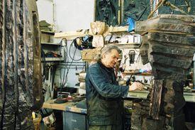 Sculptor Dimitri Hadzi (1921-2006) in his East Cambridge studio in 2003, adding patina to bronze.